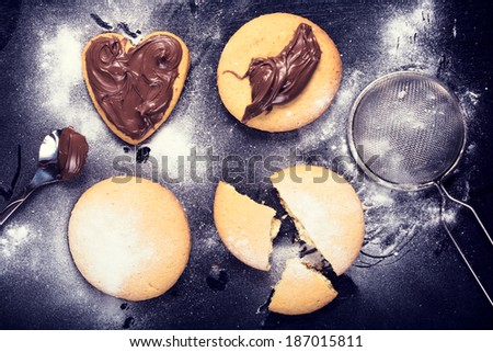 Homemade cookies with melted chocolate and sugar powder from above  - stock photo