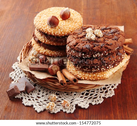 Homemade cookies with sesame seeds, chocolate, on napkin, on wooden background