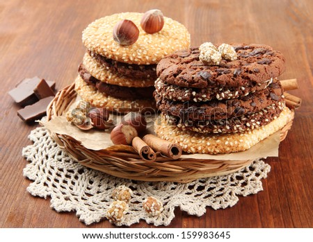 Homemade cookies with sesame seeds, chocolate, on napkin, on wooden background - stock photo