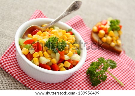 Homemade corn salsa in white bowl with spoon - stock photo