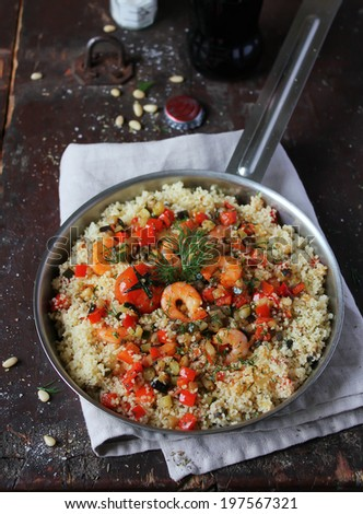 Homemade couscous with eggplant, zucchini, red pepper, cherry tomatoes, pine nuts and fresh dill in a pan ready for lunch or dinner - stock photo