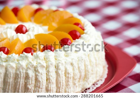 Homemade cream cake with peaches and cherries, closeup with shallow depth of field  - stock photo