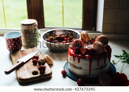 Homemade cream layer cake, fresh, colorful, and delicious dessert with juicy strawberries, sweet whipped cream and cream cheese and macaroons - stock photo