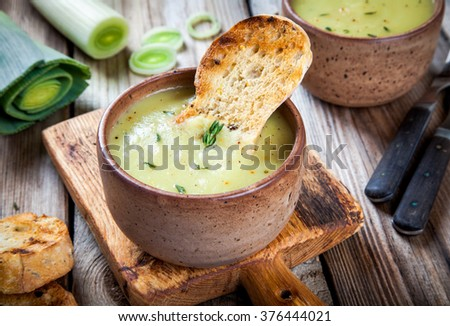 homemade cream of leek soup with croutons on wooden table - stock photo