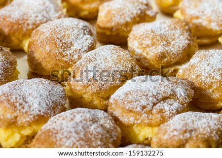 Homemade cream puffs filled with vanilla cream and sprinkled with powdered sugar. - stock photo