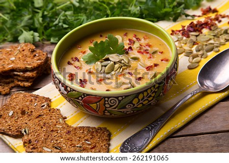 Homemade cream soup from baked butternut squash with thyme and paprika decorated with parsley and with rye crackers with pumpkin seeds and pepper - stock photo