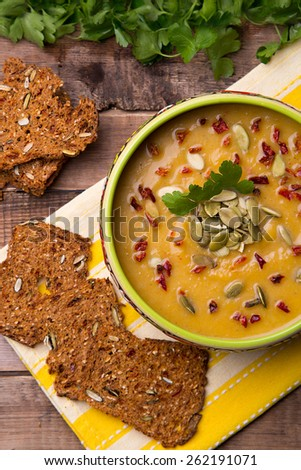 Homemade cream soup from baked pumpkin with thyme and paprika and with rye crackers with pumpkin seeds and pepper - stock photo