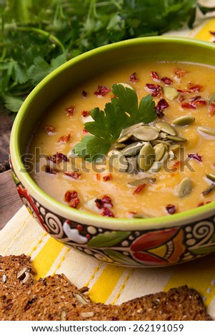 Homemade cream soup from baked pumpkin with thyme, pumpkin seeds and paprika decorated with parsley - stock photo