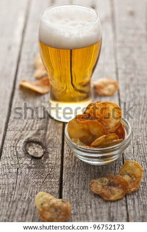 Homemade crispy potato chips with black salt and cold beer - stock photo