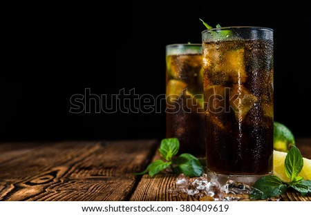 Homemade Cuba Libre with fresh lime, brown rum and crushed ice on an old wooden table - stock photo