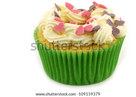 homemade cupcake with cream and  colorful candy hearts on a white background