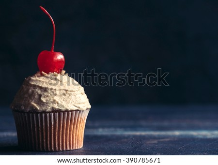 Homemade cupcake with penuts cream and cherry on the top,selective focus and copy space - stock photo