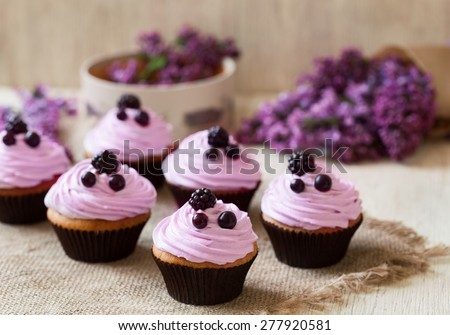 Homemade cupcakes traditional American sweet baked dessert with berries and lilac on vintage textile background. Natural light, rustic style. - stock photo