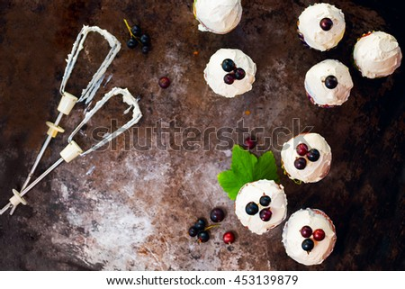 Homemade cupcakes with buttercream frosting and blackcurrant on a dark rustic background - stock photo