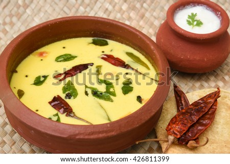 Homemade curd and spiced butter milk or butter milk or moru curry in clay pot made from cow milk with pappad / papar / pappadom in Kerala, India. Indian flavoured buttermilk. - stock photo