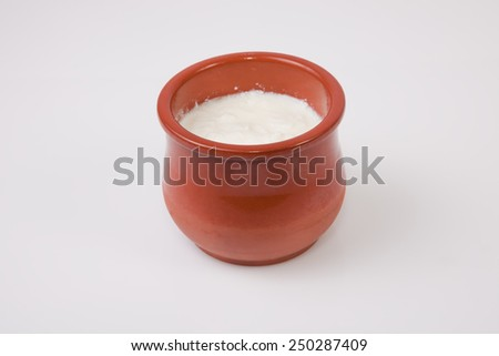Homemade curd in clay pot made from cow milk. Isolated over white background - stock photo