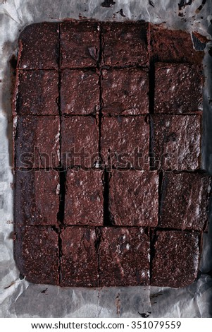 Homemade cut in squares chocolate brownie in backing pan just from oven on dark wooden background. Top view on baking sheet with dessert - stock photo