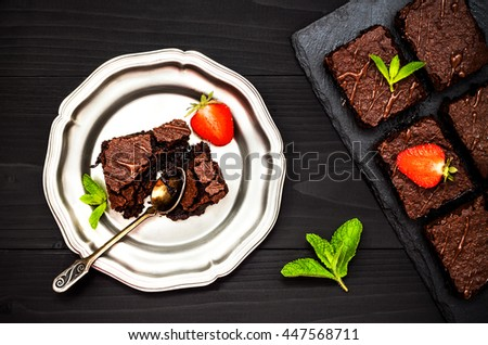 Homemade dark chocolate brownies decorated with strawberries and mint leaves over black slate background, top view - stock photo