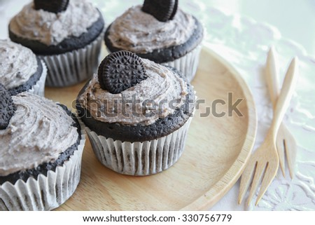 Homemade dark chocolate cupcakes with cookie and cream frosting - stock photo