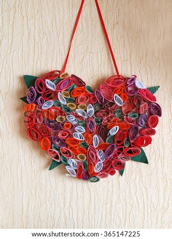 Homemade decor from small color paper rolls in heart shape hang on wall.        - stock photo
