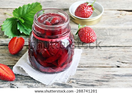 Homemade delicious strawberry jam and strawberry on a rustic wooden table - stock photo