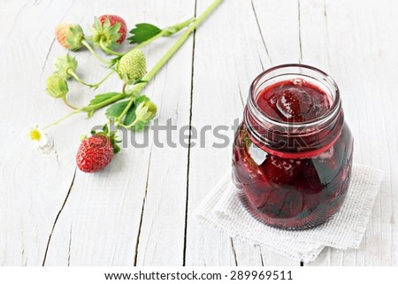 Homemade delicious strawberry jam and strawberry on a rustic wooden table.Selective focus