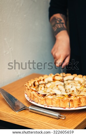 homemade delicious traditional apple pie with caramel on a plate on wood table and white background cool girl with tattoo slicing with knife trendy style