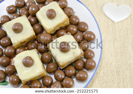 Homemade desserts in a plate decorated with chocolate balls and a white silk heart on the table - stock photo