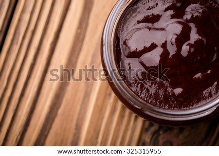 Homemade DIY natural chocolate jam made of plums, cacao powder and vanilla. Healthy marmalade in glass jar on a wooden table - stock photo