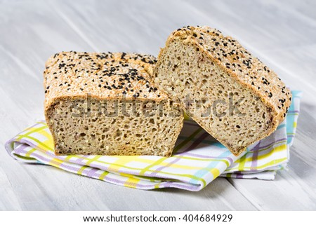 Homemade DIY natural vegan very healthy bread made of buckwheat, water, salt with black and white sesame, conopy seeds on a wooden table - stock photo