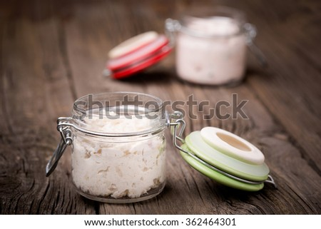 Homemade DIY natural very healthy fish, hake paste with onion and dried tomatoes, basil, chilli mixed with ricotta in a glass jar on a wooden table - stock photo