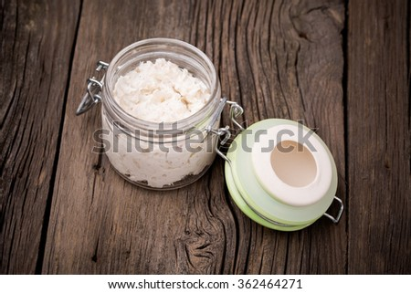 Homemade DIY natural very healthy fish, hake paste with onion and ricotta paste in a glass jar on a wooden table - stock photo