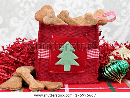 Homemade dog cookies in a decorative Christmas bag surrounded by Christmas decor. - stock photo
