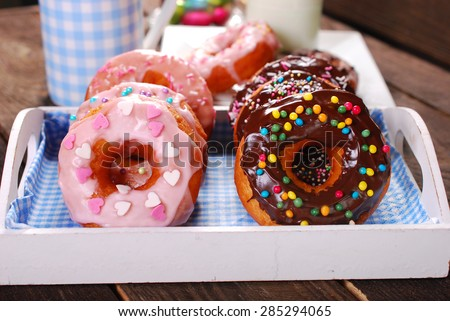 homemade donuts with chocolate and icing glaze and colorful sugar sprinkles on wooden table - stock photo
