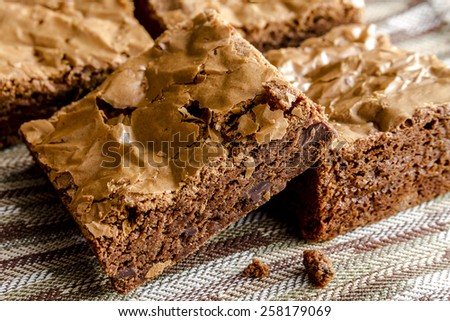 Homemade double chocolate chunk brownies sitting on brown striped napkin - stock photo