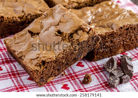 Homemade double chocolate chunk brownies sitting on white checked napkin with red hearts - stock photo