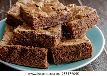 Homemade double chocolate chunk brownies stack on bright blue plate sitting on wooden table - stock photo