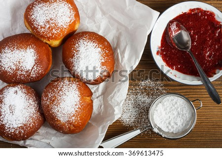 Homemade doughnuts filled with rose marmalade on wooden table. - stock photo