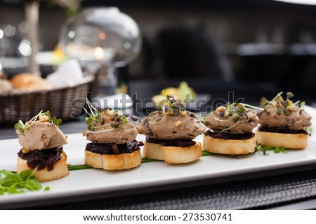 Homemade duck liver patee with cedar nuts, dried plums, bruschetta and red onion jam - stock photo