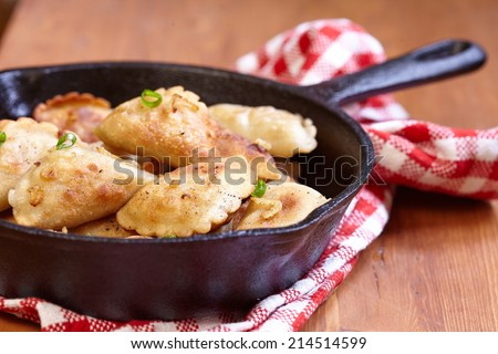 Homemade dumplings fried with onion on a pan - stock photo