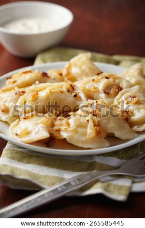 Homemade (dumplings) with potato and onion on a plate. - stock photo