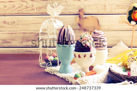Homemade easter chocolate eggs with glaze and sprinkles, retro tanned - stock photo