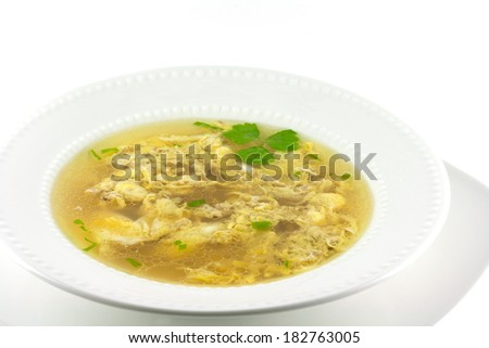 Homemade egg drop soup on a white background.