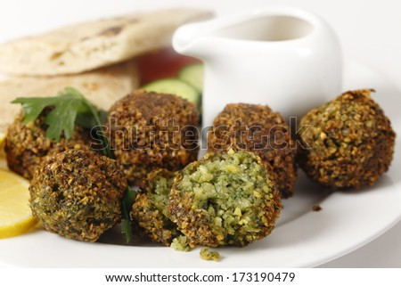 Homemade falafels (herbed and spicy chickpea balls, one broken open) on a plate with Egyptian flat bread, lemon slices, tomato, cucumber and a tahina sauce. - stock photo