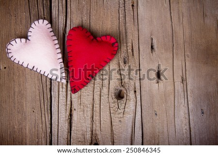Homemade felt hearts on a rustic wooden background - stock photo