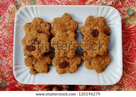 Homemade flower shaped cinnamon cookies with whole wheat, raisins and hazelnuts