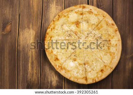 Homemade four cheese pizza with basil and oregano over wooden background. Space for text - stock photo