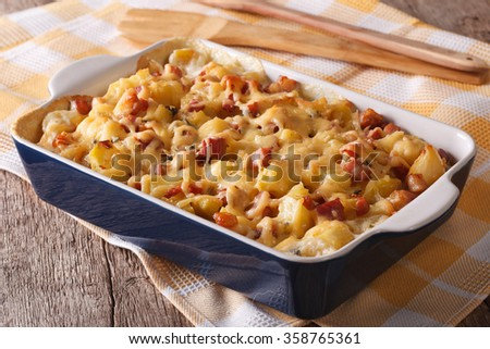 Homemade French baked potatoes with bacon and cheese close up in baking dish. horizontal