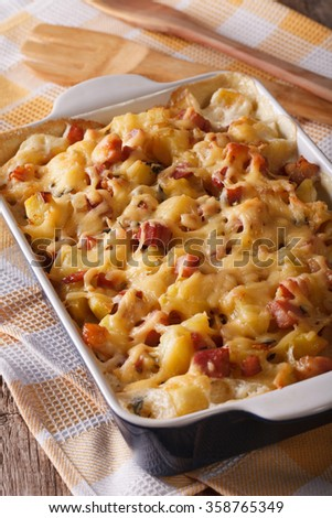 Homemade French baked potatoes with bacon and cheese close up in baking dish. Vertical