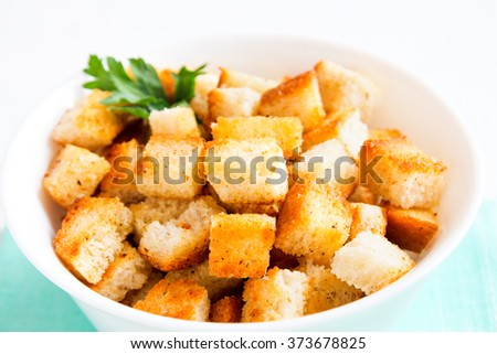 Homemade french croutons in white bowl close up
